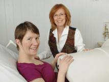 Kathleen Gustafson, profesora asociada de investigación en el Departamento de Neurología del Centro de Imágenes Cerebrales Hoglund de la Universidad de Kansas (a la derecha), con una madre en el biomagnetómetro fetal. Foto cortesía de Elissa Monroe, gerente de Servicios Fotográficos, Comunicaciones, KUMC.