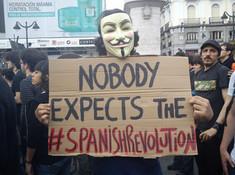 Manifestante en la Puerta del Sol de Madrid el 17 de mayo. La frase es una referencia (détournement) al clásico de Monty Python Nobody expects the Spanish Inquisition!. Fuente: Wikimedia Commons.