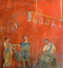 Mural de Pompeya que muestra a mujeres trabajando con un hombre en un  comercio dedicado a la lavandería y a la tintorería (fullonica). Fuente: Wikimedia Commons.