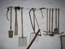 Colección de aperos agrícolas, de izquierda a derecha: hoz, pala, hachas, horcas, sierra, rastrillo, pico y azadas. Recogidos en Cuenca, España. Fuente: Wikimedia Commons.