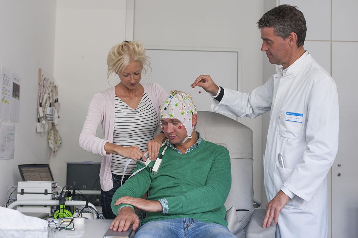 Laura Tiemann, primera autora del estudio, junto con Markus Ploner, investigan del dolor humano con un voluntario sometido a las mediciones del EEG. (Imagen: K. Bauer / TUM).