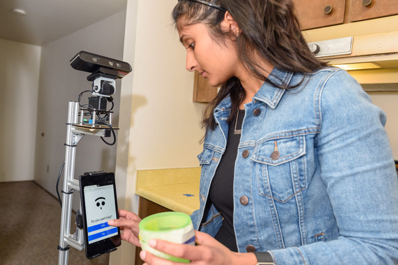 La estudiante Nisha Raghunath demuestra las interacciones entre un humano y un robot auxiliar en la Smart Apartment de la WSU, en Pullman. El robot detecta cuándo el sujeto comete un error en las tareas diarias y ofrece asistencia para ayudar a la persona a realizarlas. Imagen: Washington State University.