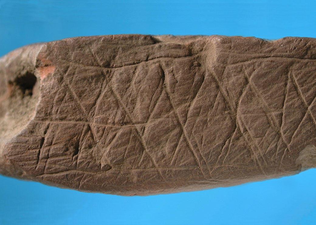 Trozo de ocre grabado con un patrón abstracto en el sitio de Blombos (Sudáfrica) con una antigüedad de 75,000 años. © D'Errico / Henshilwood / Nature. Universidad de Burdeos.