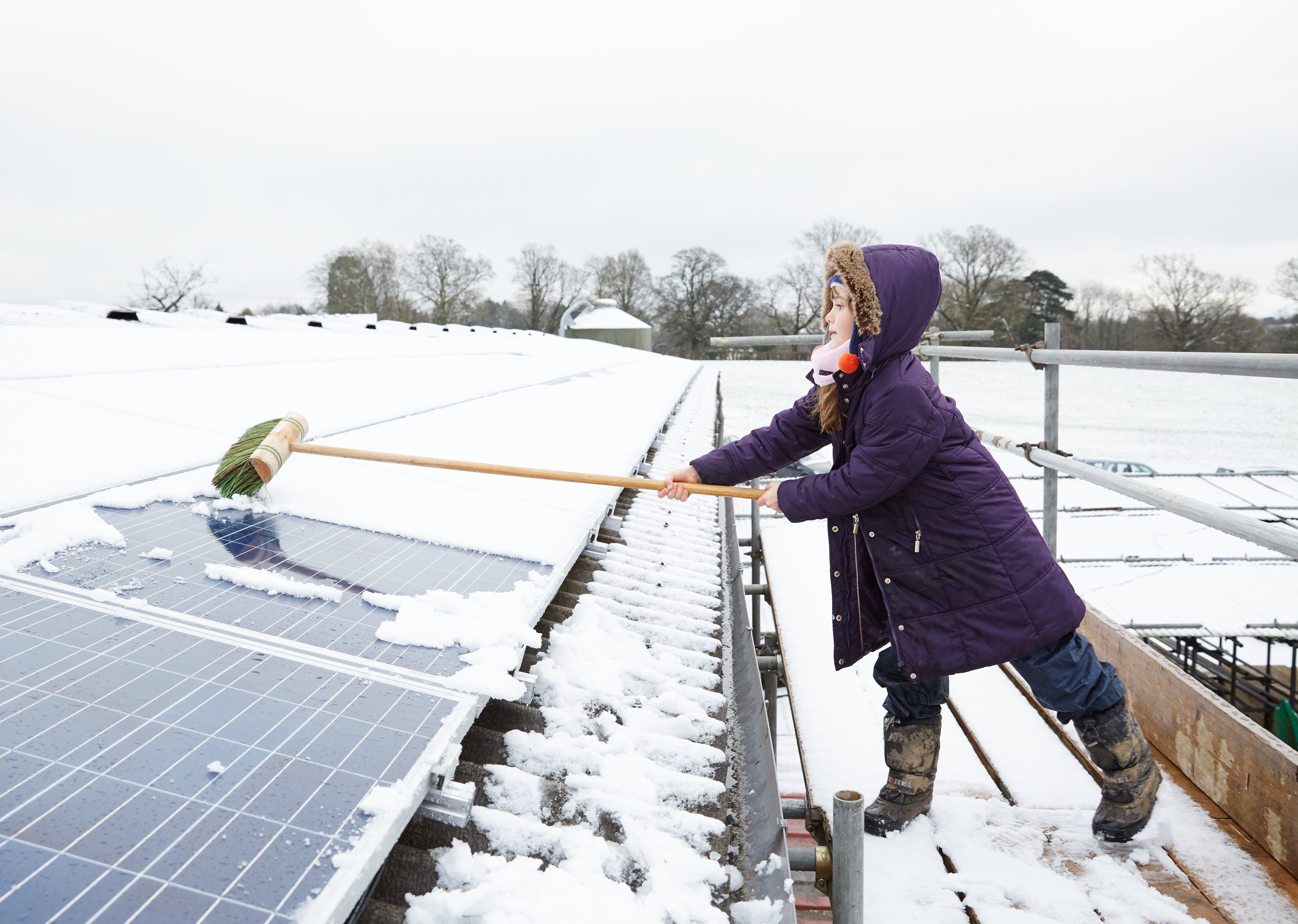 Niña limpiando paneles solares fotovoltaicos de la nieve en Grange Farm, Balcombe, Reino Unido. Foto: Balcombe.