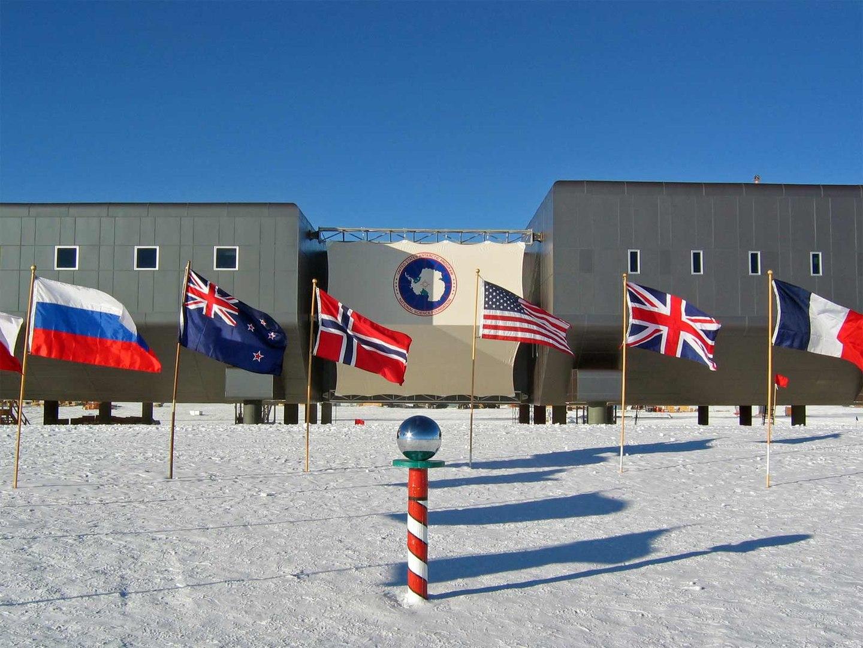 Banderas de los firmantes del Tratado Antártico en la Base Amundsen-Scott y la señal que indica el llamado Polo Sur Geográfico Ceremonial. Foto: Bill Spindler, U.S. Antarctic Program, National Science Foundation.