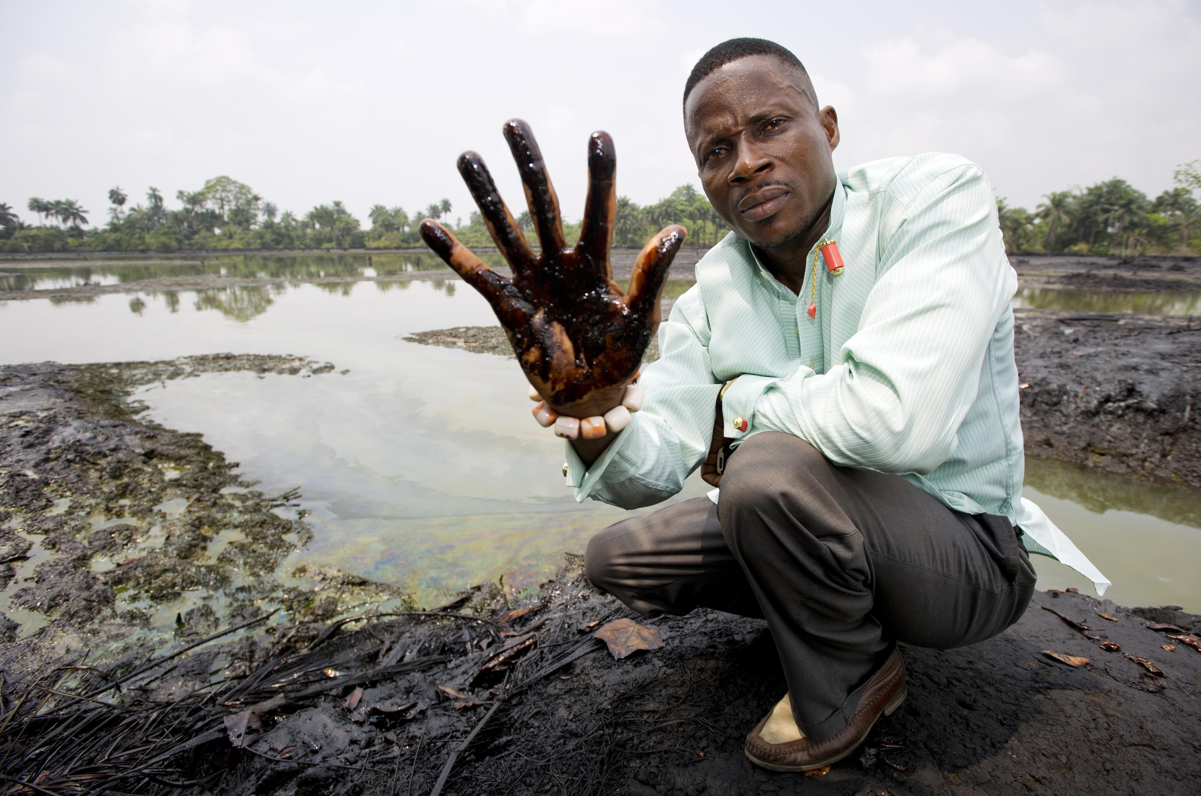 """Eric Dooh, en el pueblo de Goi, Ogoniland, mostrando la contaminación del mar por el petróleo debido a una actividad de la empresa Shell en Nigeria. Fuente: """"Marten van Dijl/Friends of the Earth Netherlands"""