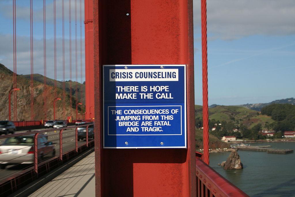 Cartel en el puente Golden Gate (California, EE.UU.) que advierte de las consecuencias de saltar por el puente y recomienda llamar a un teléfono de ayuda mediante un aparato situado allí mismo. Imagen: Miskatonic. Fuente: Wikipedia.