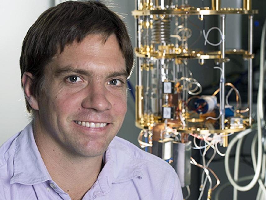 Kater Murch, junto al congelador de diluciones que ha utilizado para enfrir su qubit superconductor. Imagen: Joe Angeles. Fuente: WUSTL.
