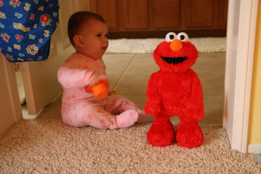 Un bebé con un muñeco Elmo. Imagen: Marc Levin. Fuente: Flickr.